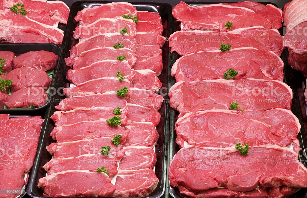 Rows of raw beef steaks with garnish stock photo