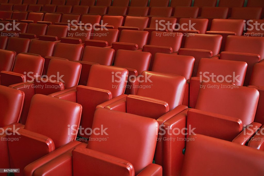Rows of red folding chairs stock photo