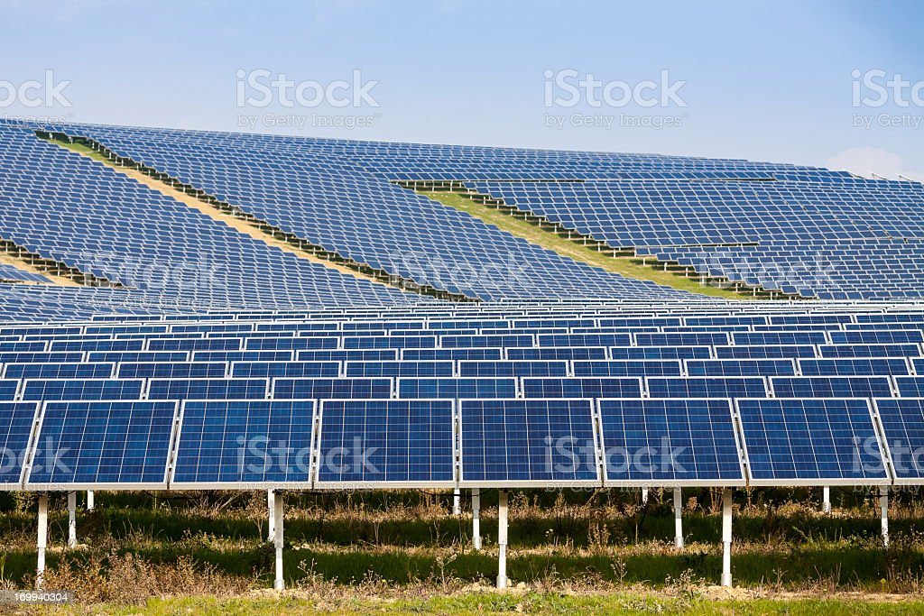 Rows of solar panels along the hillside stock photo