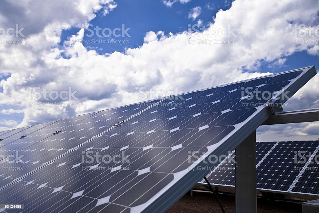 Rows of solar panels on roof under the blue sky with clouds royalty-free stock photo