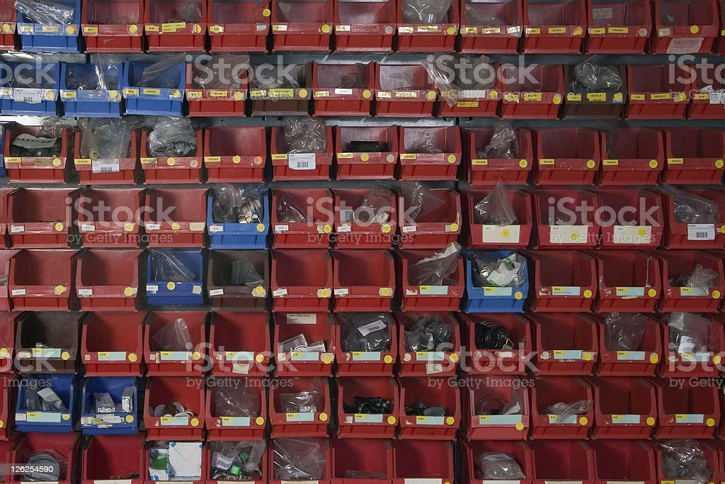 Rows of spare parts storage tubs in red and blue royalty-free stock photo