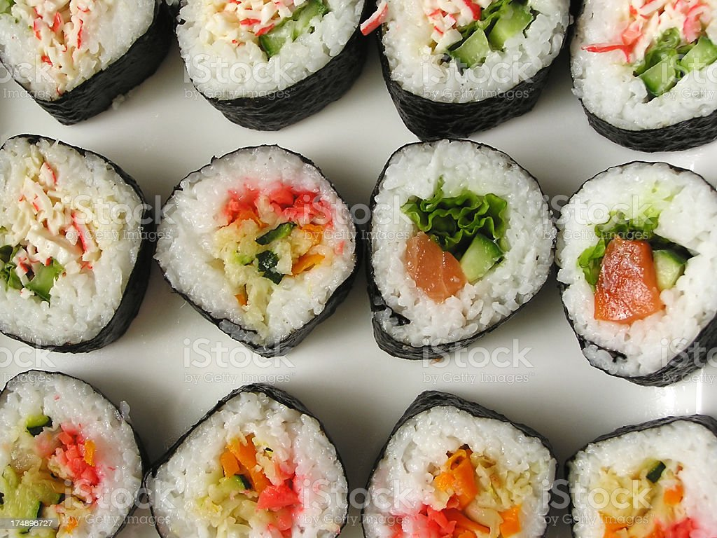 Rows of sushi rolls on flat surface stock photo