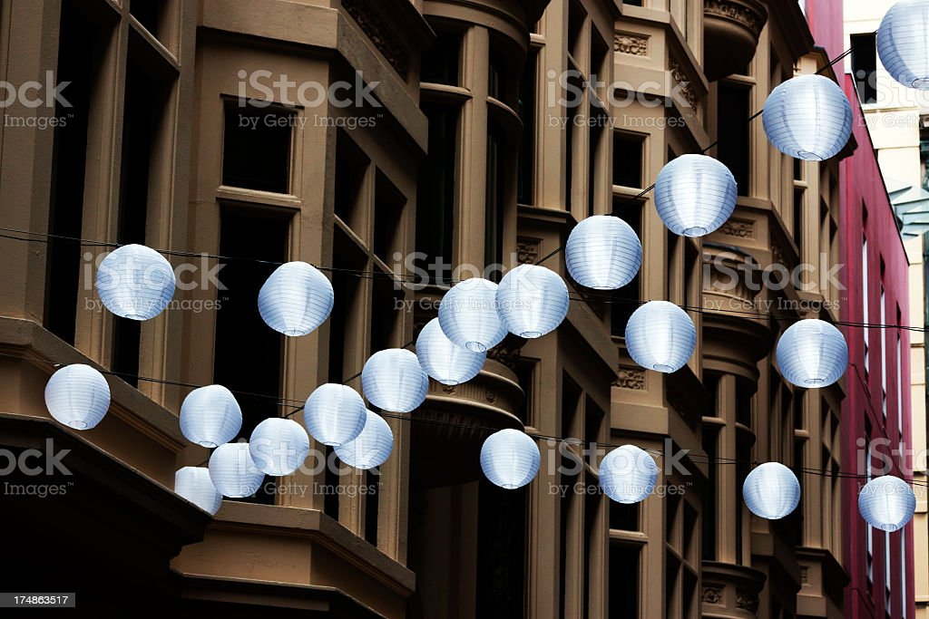 Rows of white chines lantern hanging on street between buildings royalty-free stock photo