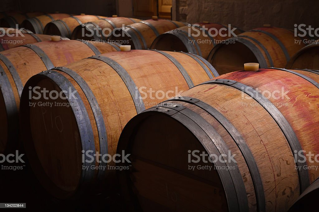 Rows of wine barrels aging in a cellar stock photo