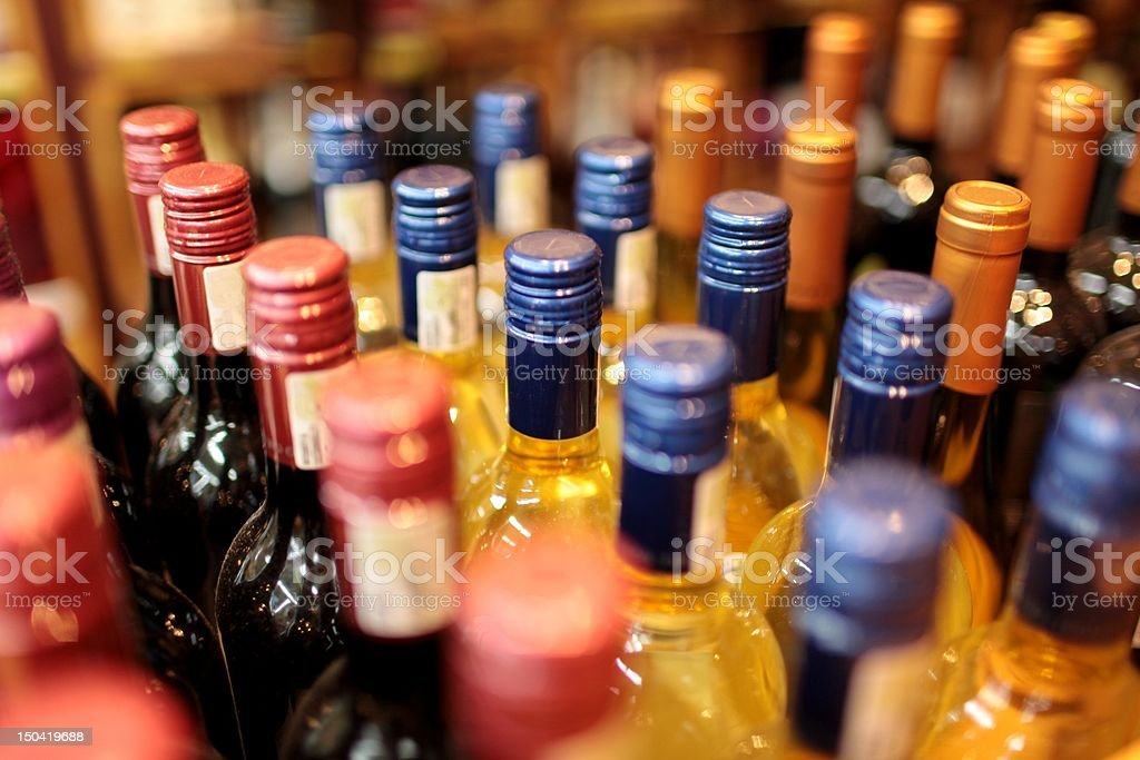 Rows of wine bottles with colorful tops stock photo