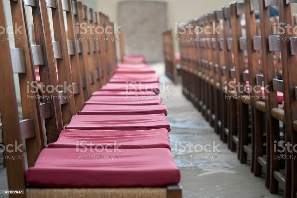Rows of Wooden chairs with red pillows royalty-free stock photo