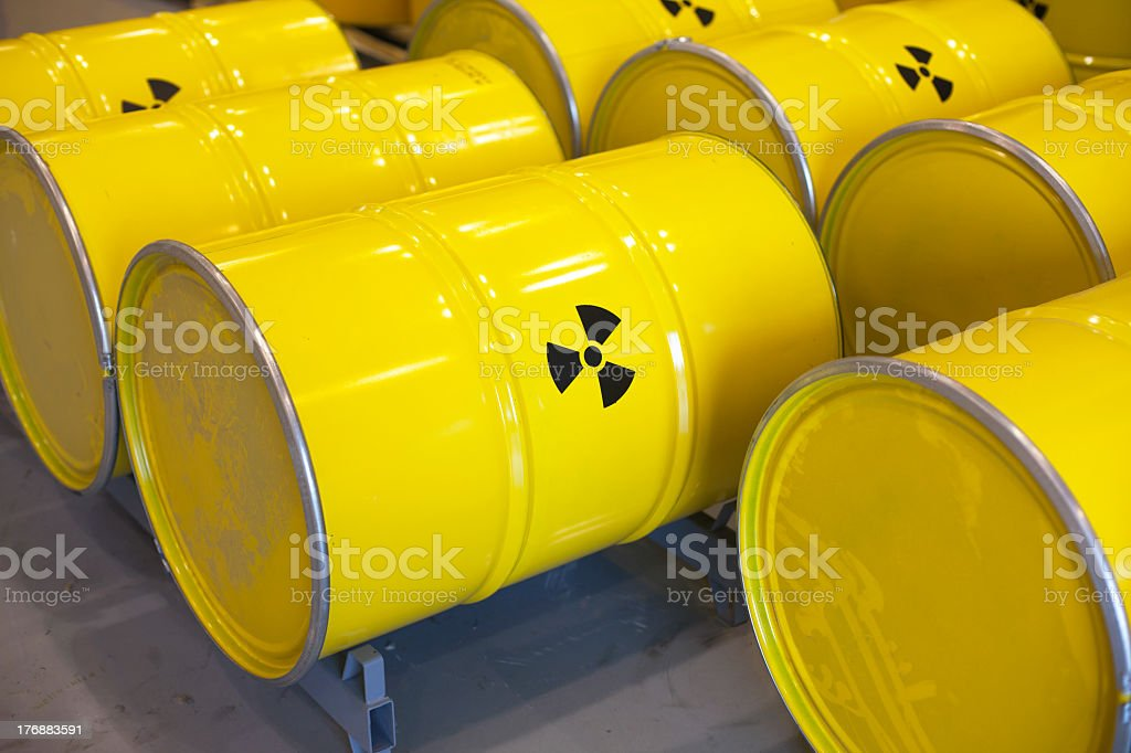 Rows of yellow barrels of radioactive waste stock photo