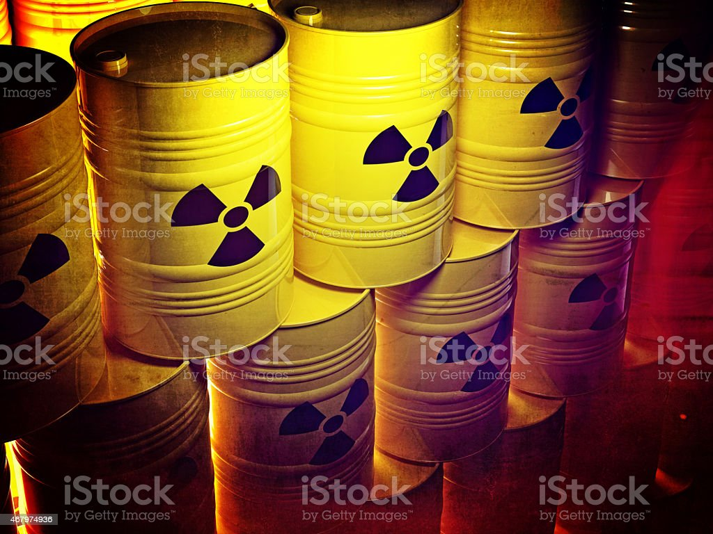 Rows of yellow barrels with the radioactive danger sign stock photo
