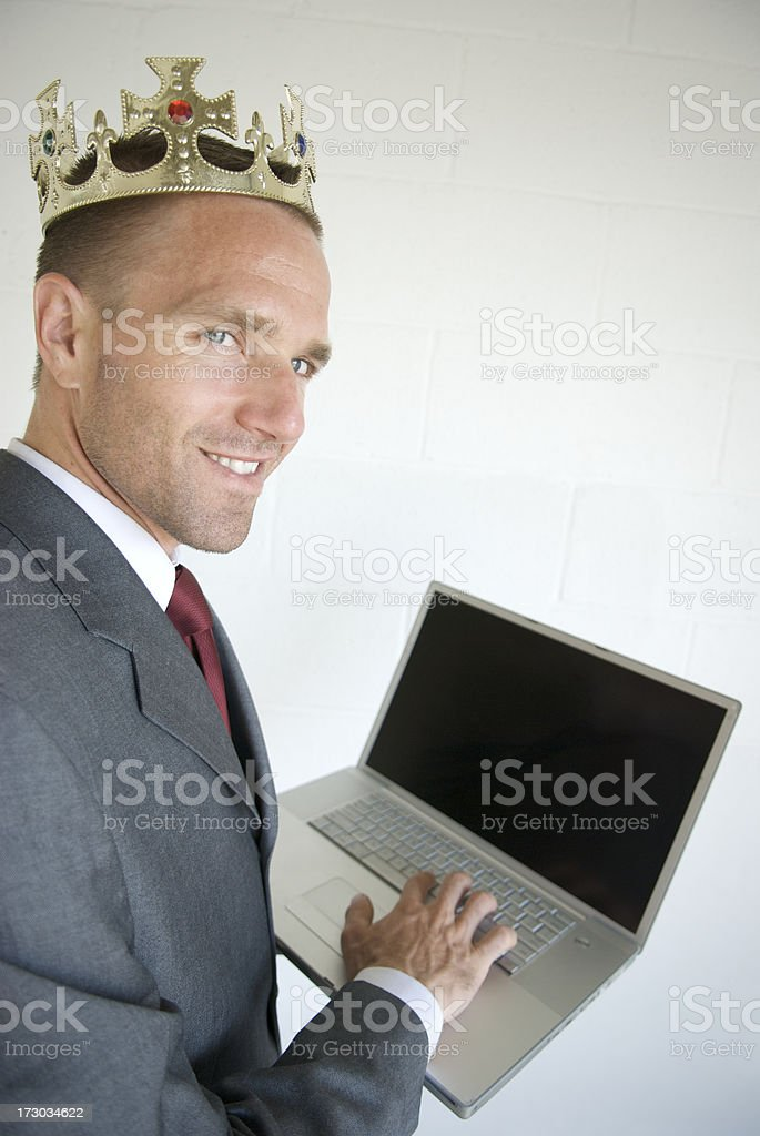 Royal Businessman Smiling with Crown and Blank Laptop Announcement Message royalty-free stock photo
