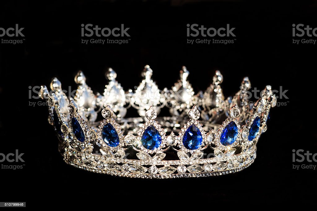 Royal crown with sapphire on black background. Monarchy stock photo