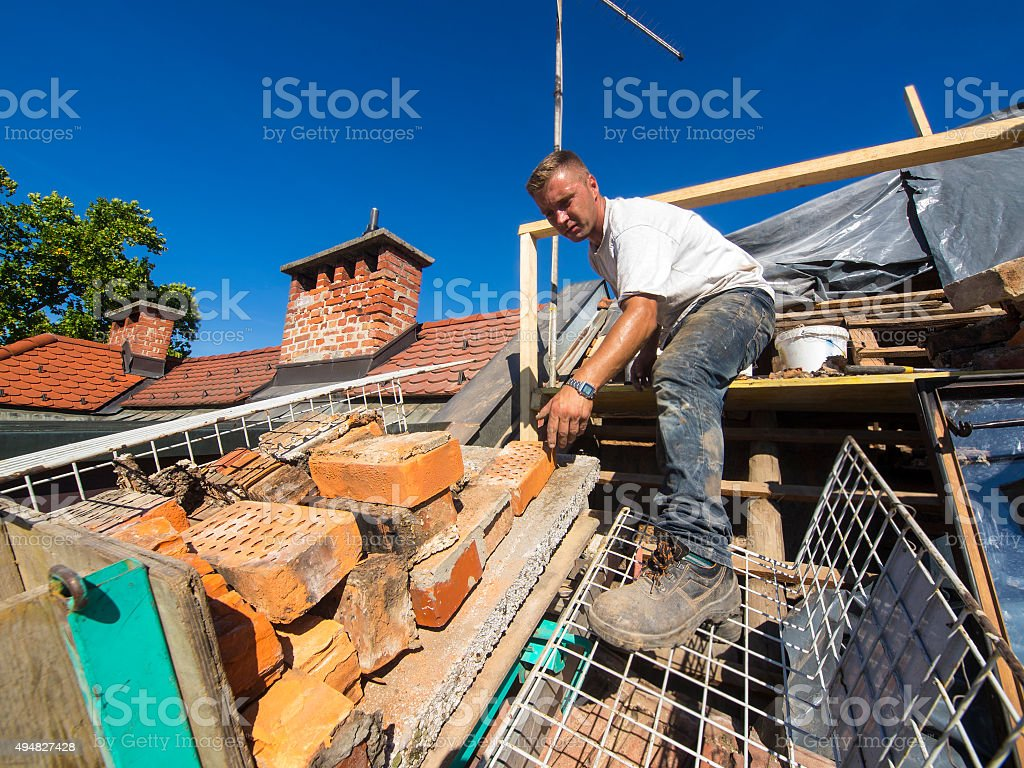 Rreplacing two brick chimneys on an old roof stock photo