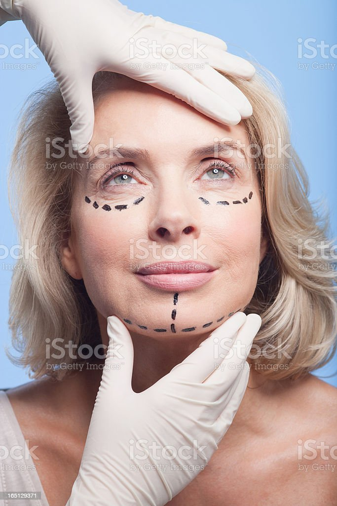 Rubber-gloved hands holding woman's face with dotted lines stock photo