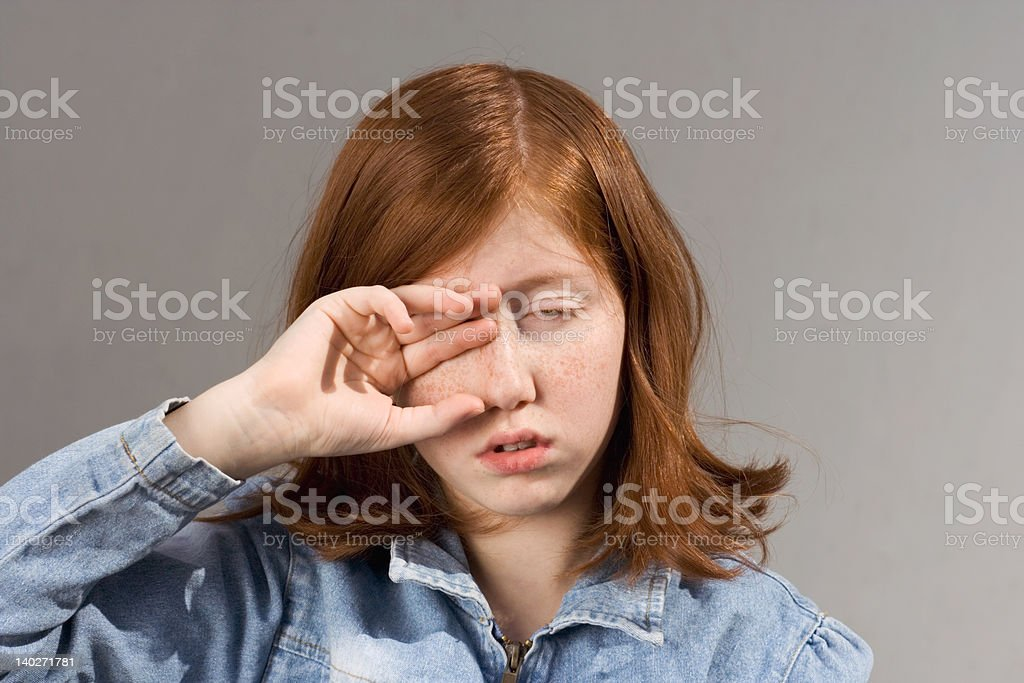 rubbing eyes - girl with red hair stock photo