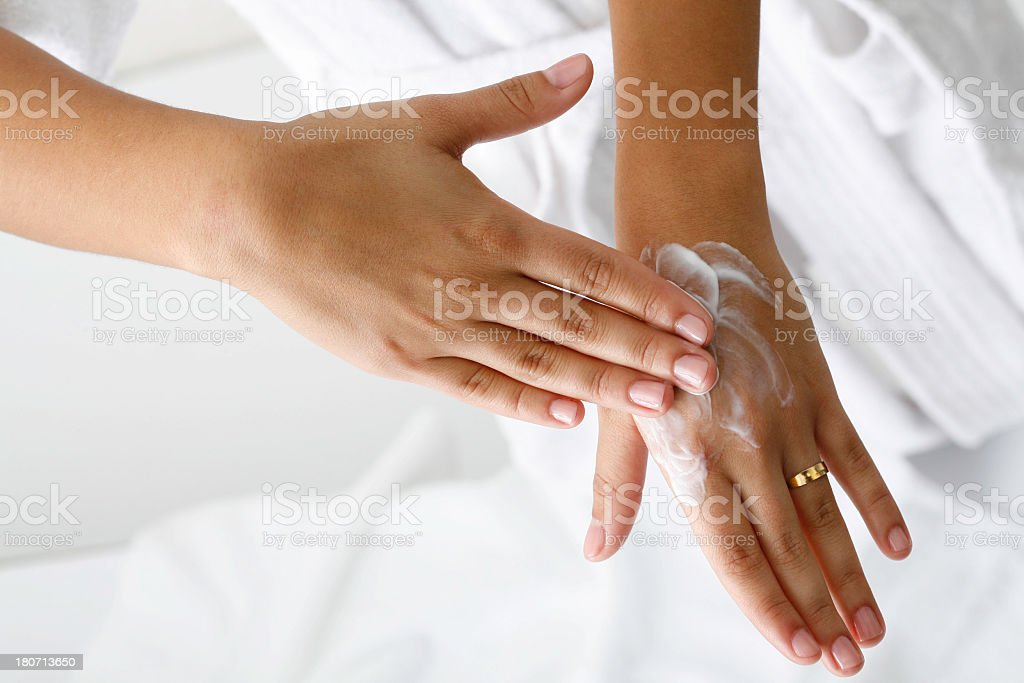 Rubbing lotion on hands to keep soft stock photo