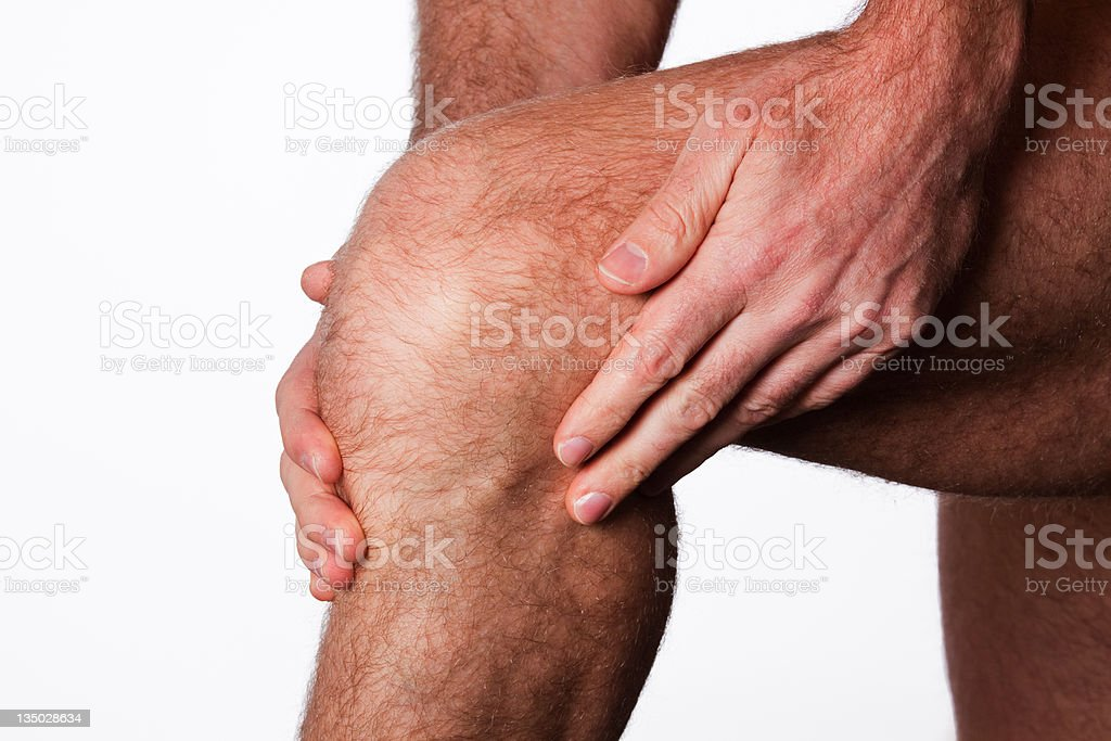 Rubbing sore knee with both hands stock photo