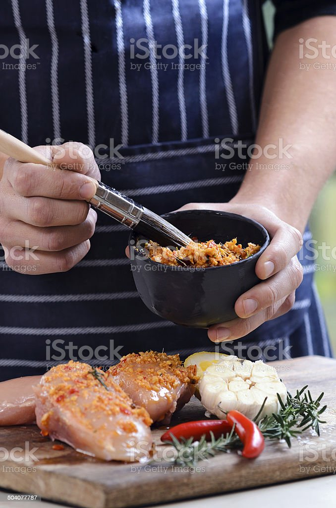 Rubbing spice mixture on raw chicken breasts stock photo