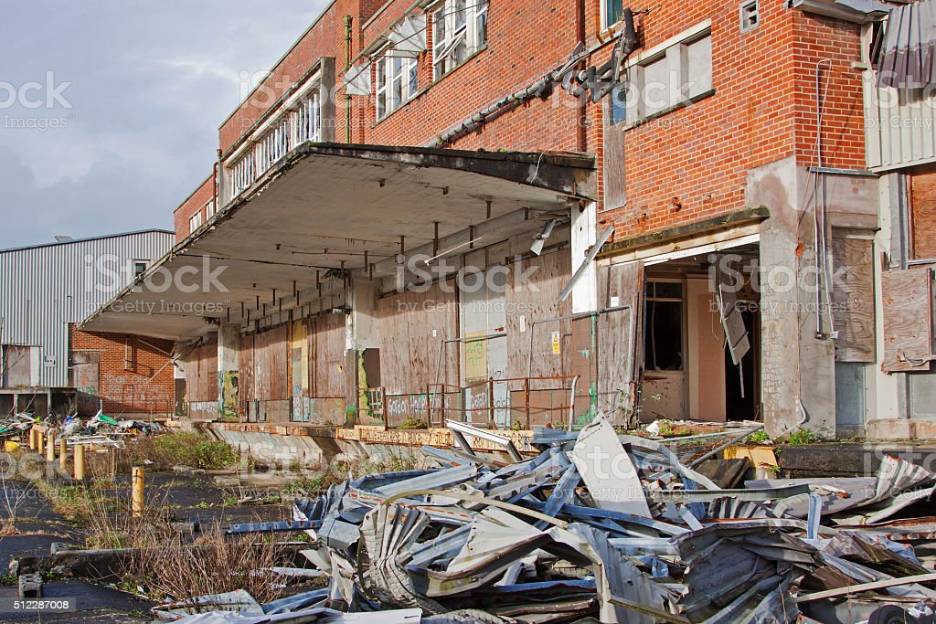 Rubble lying around the forecourt of a disused factory UK stock photo