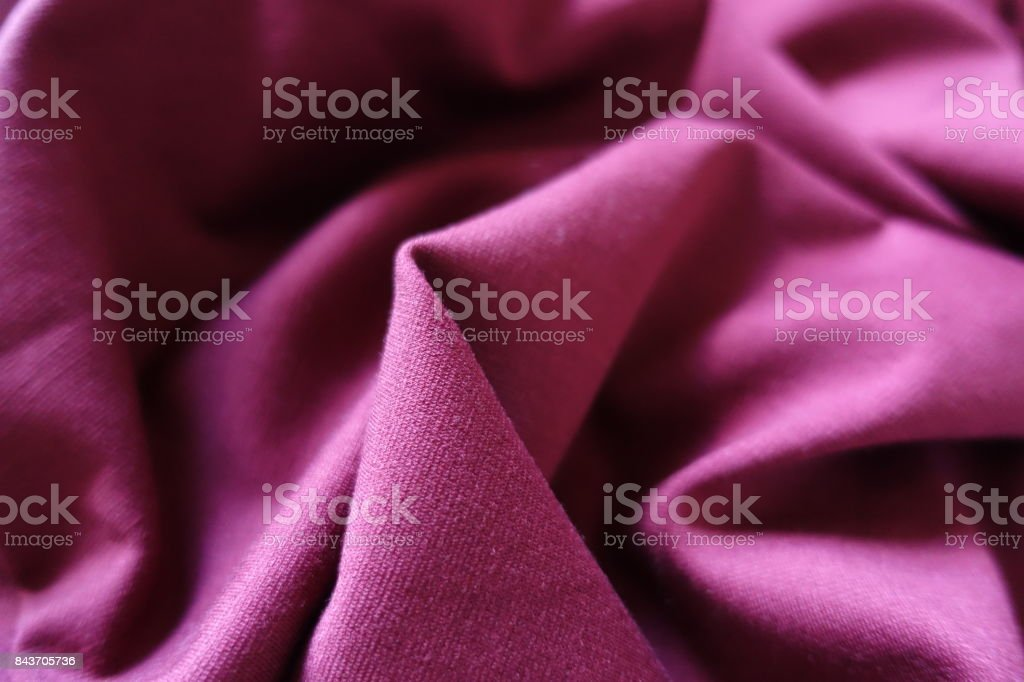 Ruby colored stockinette fabric in soft folds stock photo