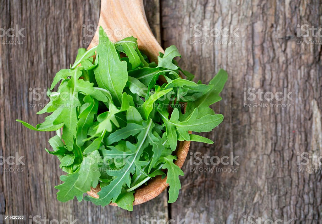 rucola in a wooden spoon stock photo