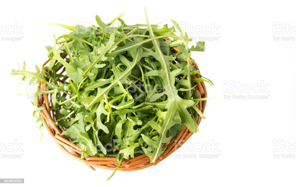 Rucola plant in a wicker bowl isolated stock photo