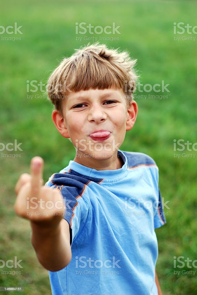 Rude little boy sticking out tongue and flipping off camera stock photo