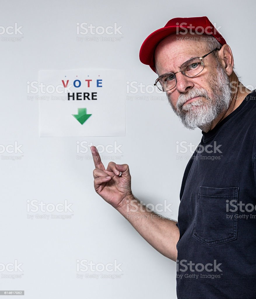 Rude Redneck Man Flipping The Bird at VOTE HERE Sign stock photo