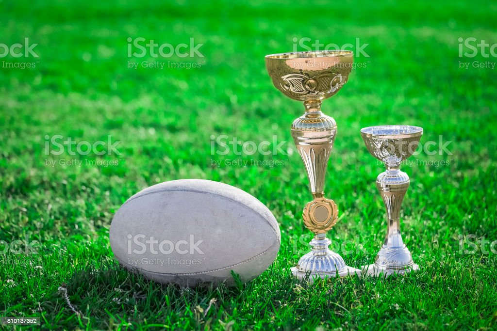 Rugby ball and rugby trophies on grass stock photo