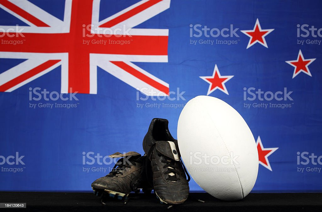 Rugby ball and shoes in front of New Zealand flag backdrop stock photo