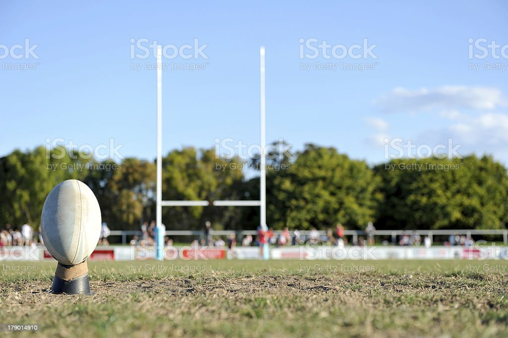 Rugby ball placed on a kicking tee with goal posts in the background