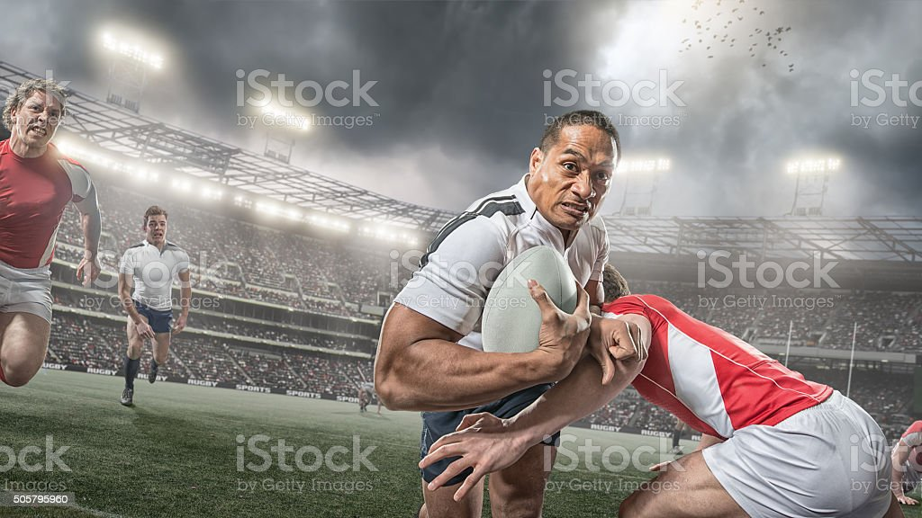 Rugby Player Running With Ball Whilst Being Tackled During Game stock photo