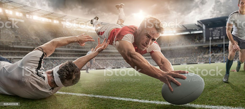 Rugby Player Scoring and Being Tackled in Mid Air Dive stock photo