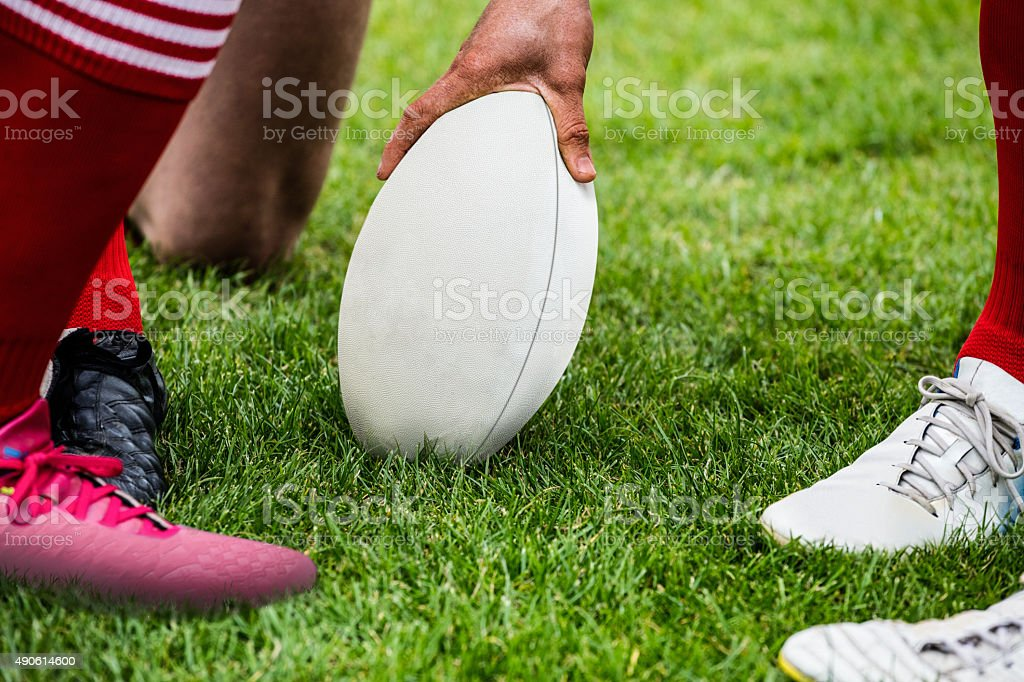 Rugby players in huddle with ball stock photo