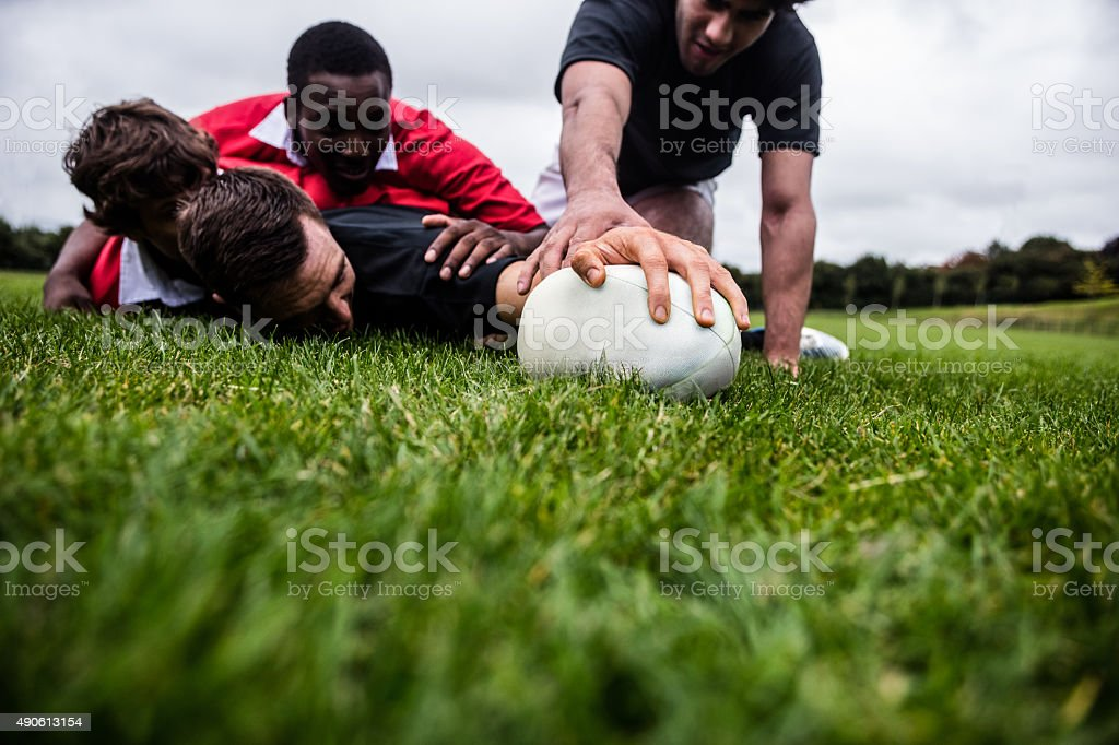 Rugby players tackling during game stock photo