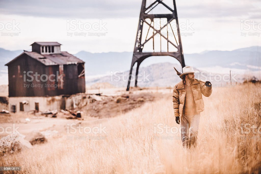 Rugged man carrying pickaxe over shoulder walking through western field royalty-free stock photo