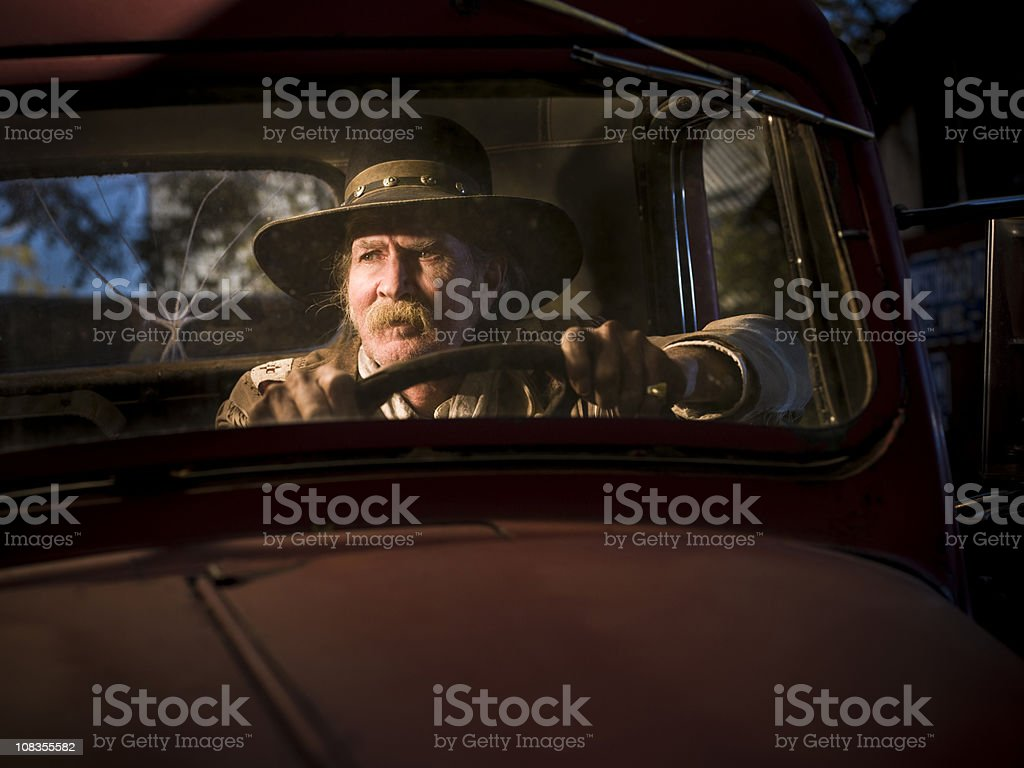 Rugged man sitting in old truck royalty-free stock photo