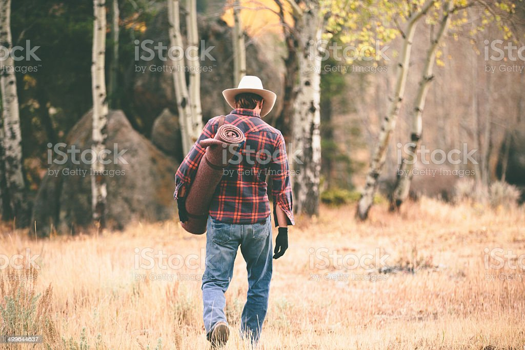 Rugged man walks away through woods carrying blanket stock photo
