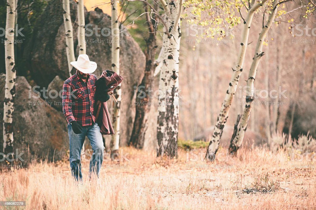 Rugged man walks through woods carrying blanket and looking down stock photo