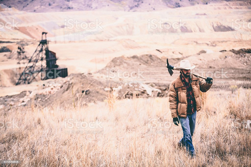 Rugged man with pickaxe over shoulder walks through industrial field stock photo