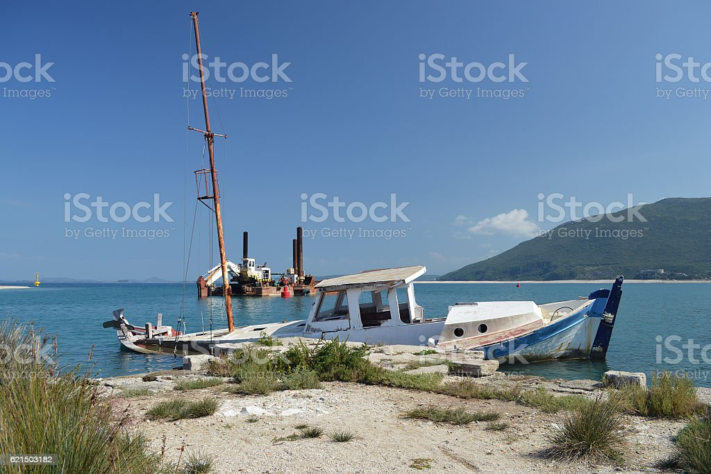 Ruined boat and old dredge stock photo