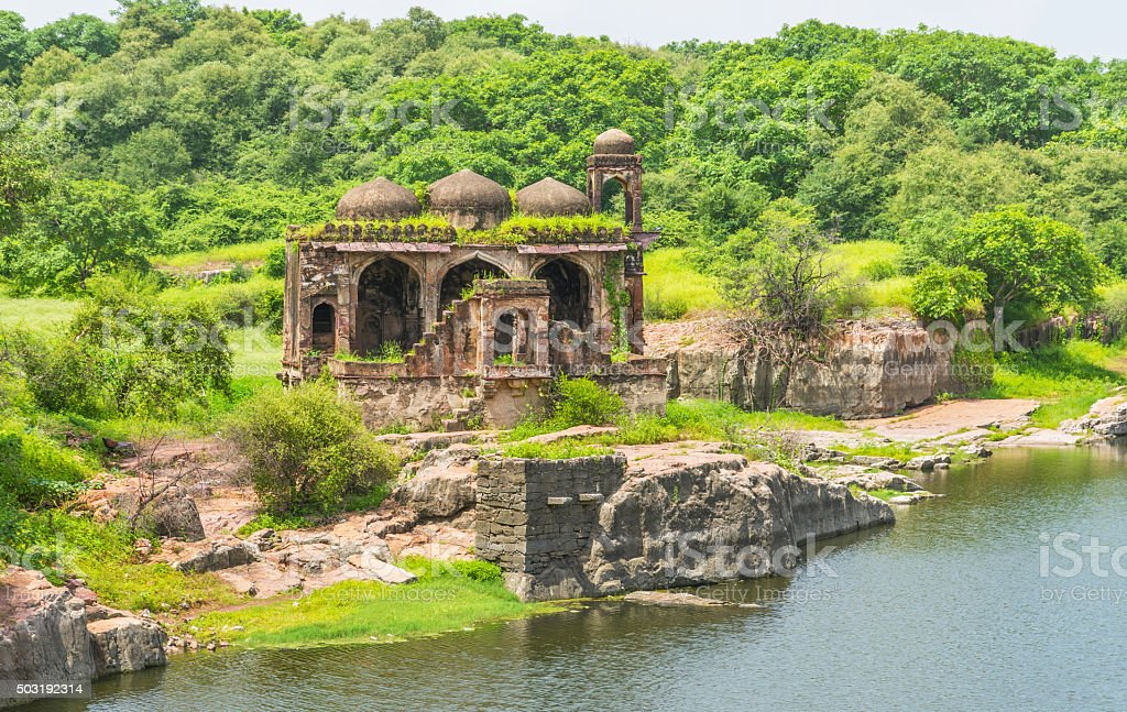 Ruined mosque along water tank stock photo