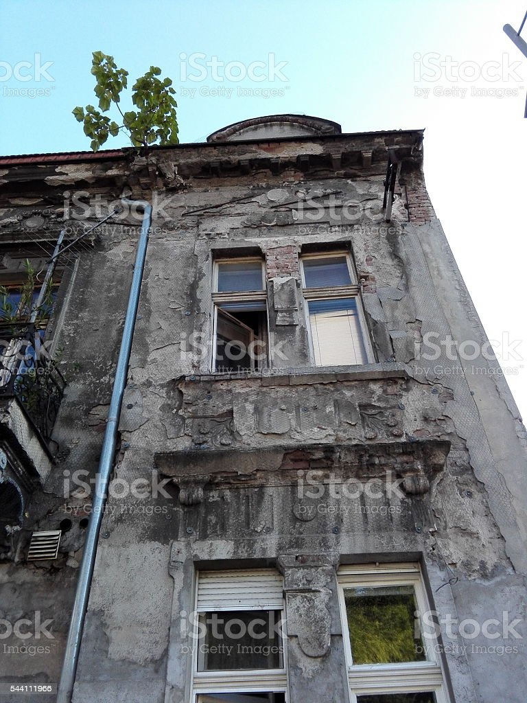 Ruined window balcony wrapped with protective wire metal mesh stock photo