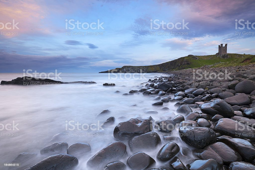 Ruins of Dunstanburgh Castle from the rocky beach at dusk stock photo