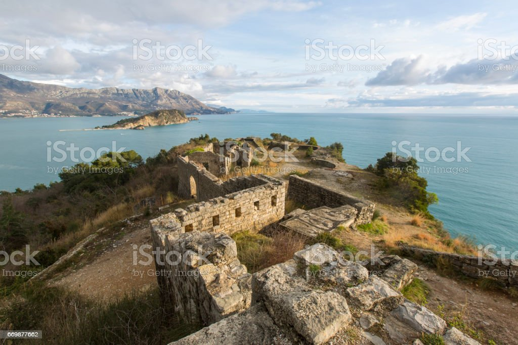 Ruins of medieval fortress Mogren at the shore of Adriatic sea. Historic attractions of Budva, Montenegro. stock photo
