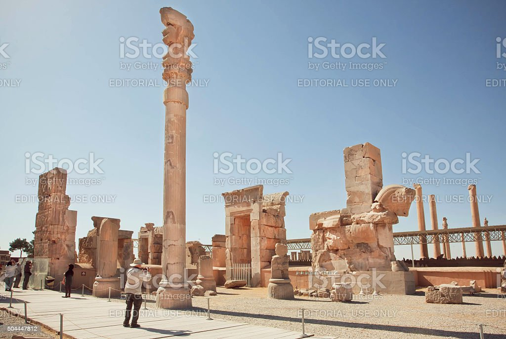 Ruins of Persepolis and tourists making photopictures stock photo