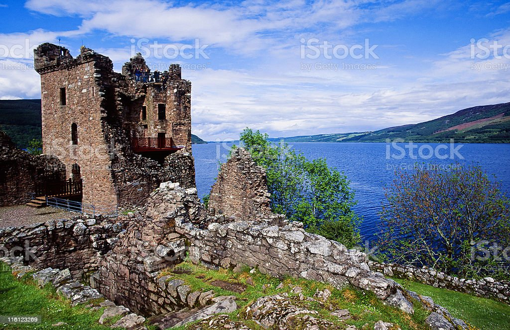 Ruins of Urquhart Castle on the hill next to blue waters stock photo