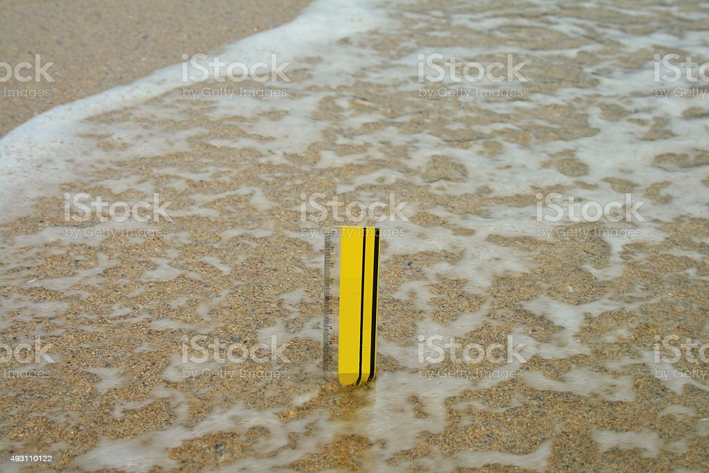 Rule measuring the current sea level rise stock photo