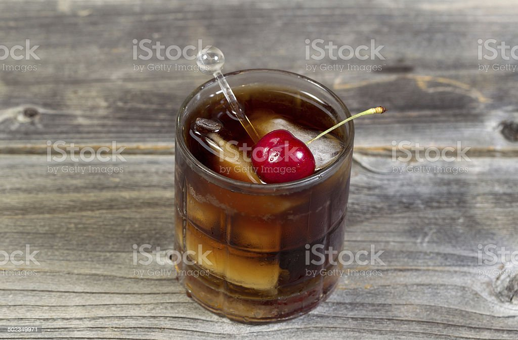 Rum and Cola with large red cherry stock photo