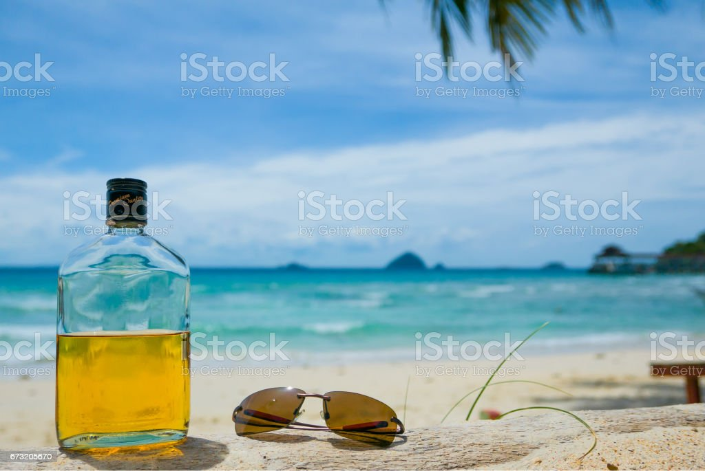 rum and sunglasses on sunny beach stock photo