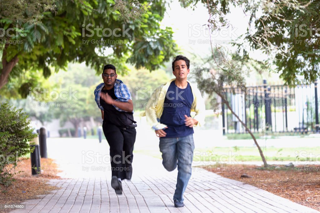 Run fast mate, we are late for our game. stock photo
