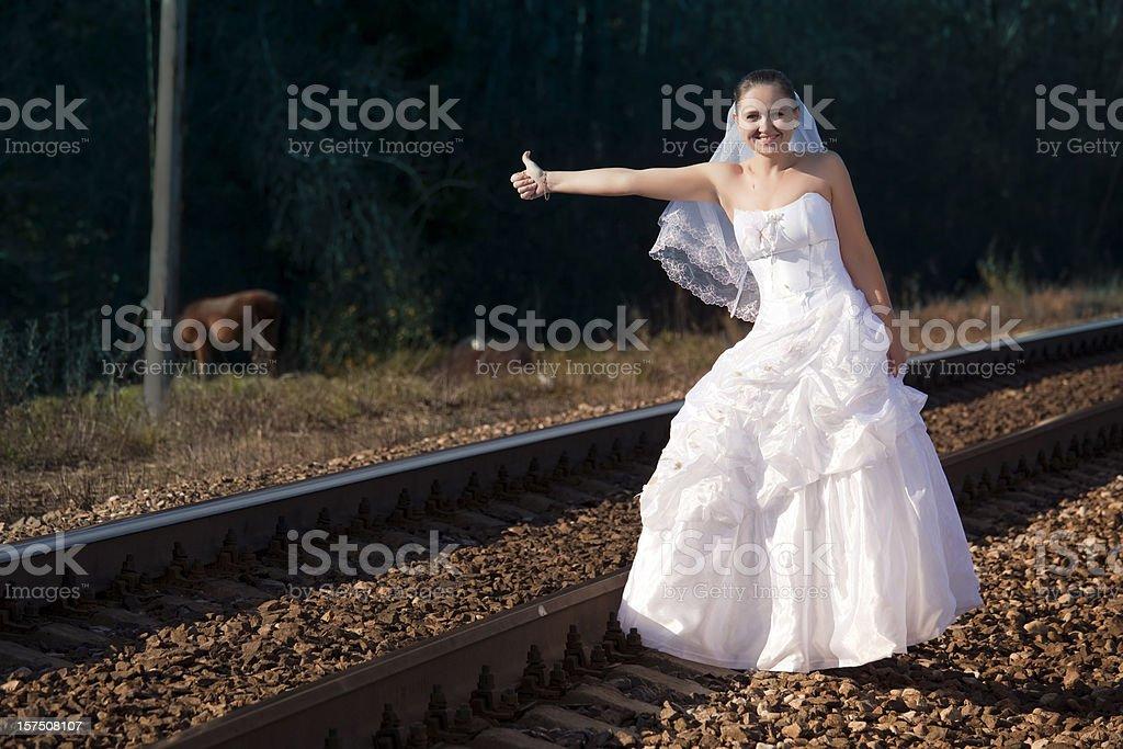 Runaway Bride. Beautiful woman stopping a train stock photo